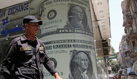 A policeman walks past a currency exchange bureau advertisement showing images of the U.S dollar and other currencies in Cairo, Egypt August 3, 2016. Picture taken August 3, 2016.   REUTERS/Mohamed Abd El Ghany - RTSMD9F