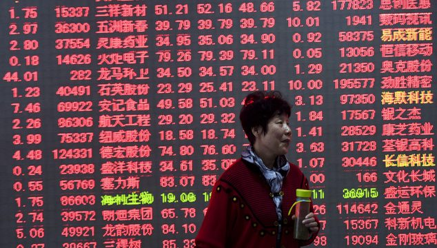 A woman holds a bottle of tea in front of an electronic board displaying stock prices at a brokerage house in Hangzhou in east China's Zhejiang province, Thursday, Nov. 10, 2016. Asian shares rallied Thursday, extending a surprising global recovery as U.S. President-elect Donald Trump's conciliatory acceptance speech comments helped soothe world financial markets spooked by his unexpected U.S. election victory. (Chinatopix via AP)