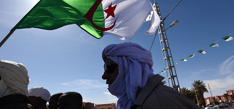 A demonstrator waves an Algerian flag during a sit-in on March 5, 2015 at Somoud Square in the Sahara desert village of In-Salah, south Algeria, to protest against the exploration of shale gas. Anti-shale gas demonstrations have increased in the cities of the Algerian Sahara since late December, when Algerian oil company Sonatrach announced it had successfully completed its first pilot drilling in the In-Salah region. Sonatrach announced in early February that its exploratory drilling for shale gas using hydraulic fracturing would continue despite mounting hostility among people living nearby. AFP PHOTO / FAROUK BATICHE        (Photo credit should read FAROUK BATICHE/AFP/Getty Images)